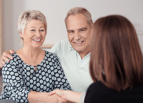 Older couple shaking hands with a woman